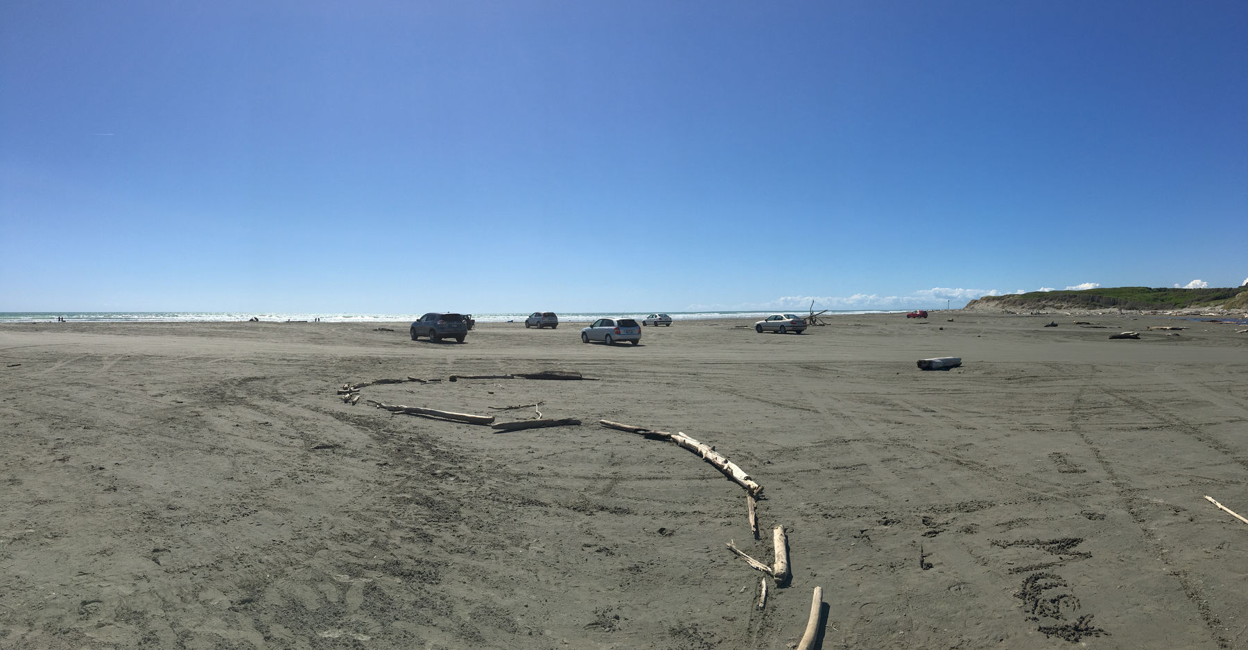 A photo of several cars parked up on a beach, with the waves crashing in the background in the mid afternoon on a beautiful late spring day