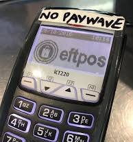 An EFTPOS terminal with a hand-written sticker at the top of the unit