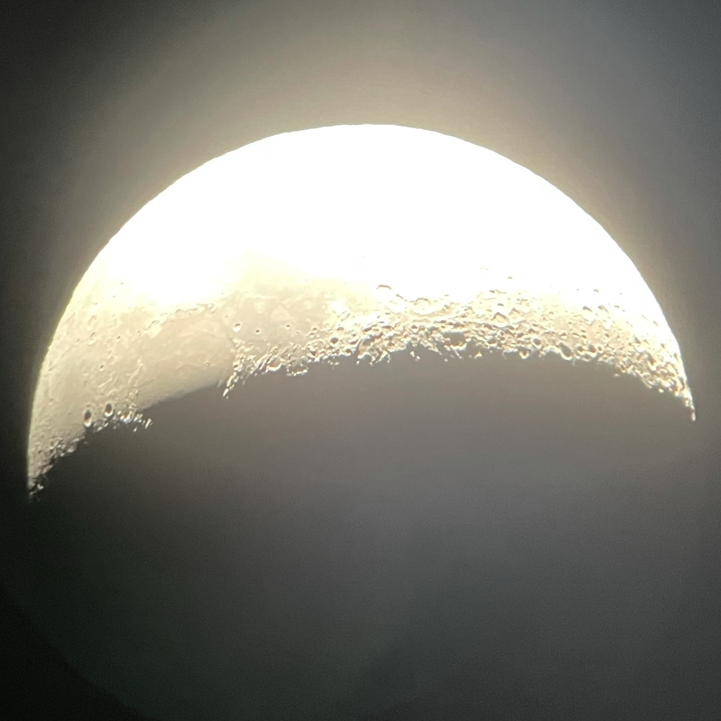 The moon, in epic detail through a telescope. The teleif of the sirface features are stark and the detail in the relief of surface features make it look loke you could run your fingers along the sueface.
