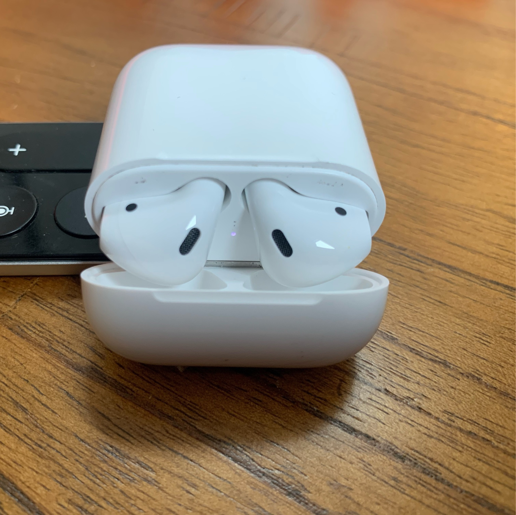 My brand new Airpods (second gen) in my original charging case, sitting open on a wooden table.